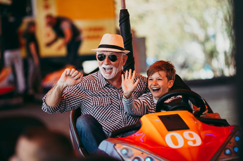 old man and child riding bumper cars